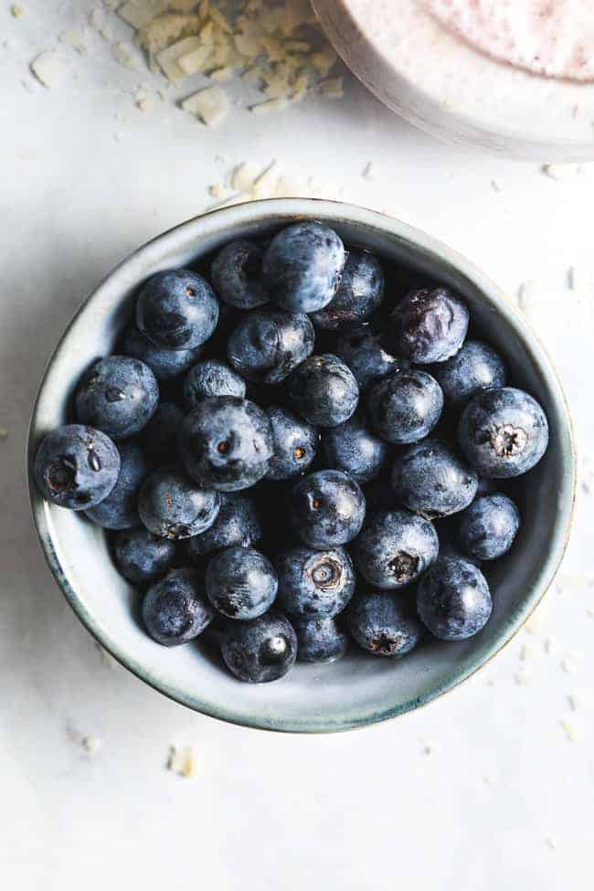 bowl of fresh blueberries on a white table