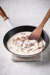 bacon into cream in a pan