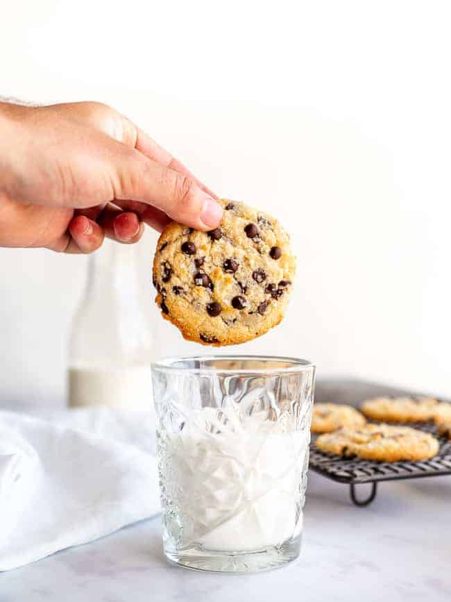 hand holding a chocolate chip cookie over a glass of milk