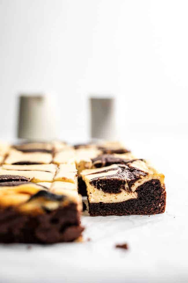 cheesecake brownie on parchment paper with bottles in background