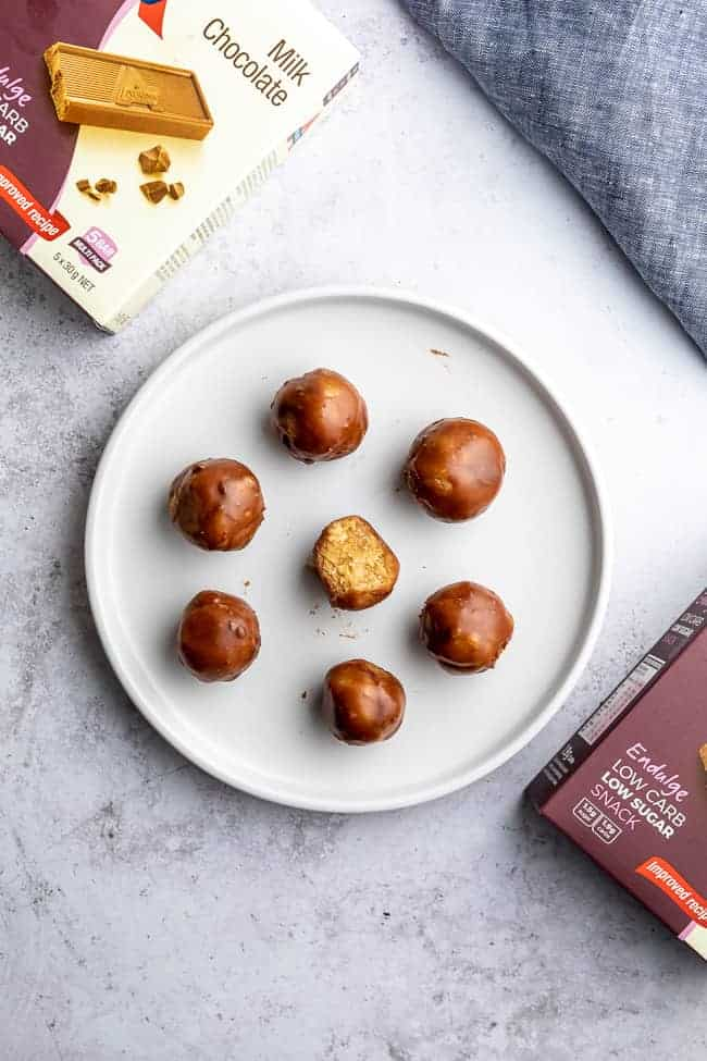 peanut butter balls on white plate with one facing upwards