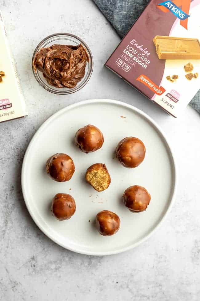 low carb peanut butter balls with swirl of chocolate on grey background with box in top corner