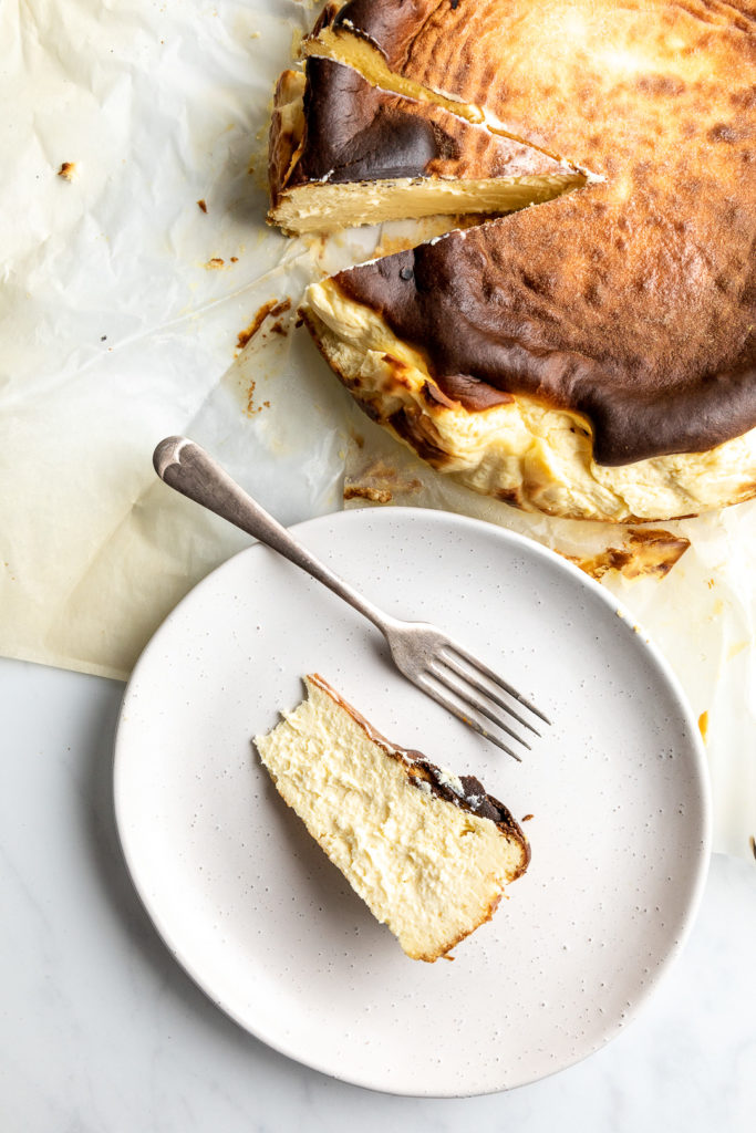 basque burnt cheesecake on white plate and parchment paper