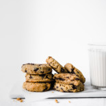 keto pumpkin chocolate chip cookies with milk on white background